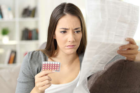 Foto de Worried woman reading contraceptive pills leaflet sitting on a couch at home - Imagen libre de derechos