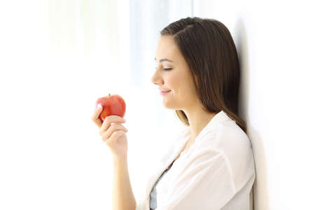 Photo pour Side view portrait of a woman looking at an apple isolated on white at side - image libre de droit