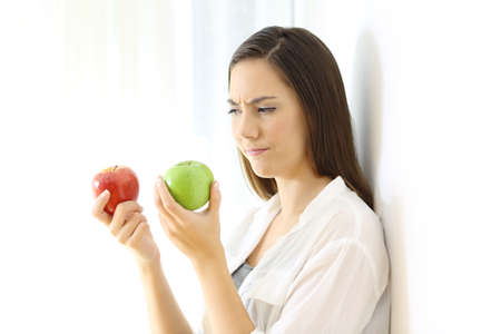 Photo for Doubtful woman deciding between red and green apples isolated on white at side - Royalty Free Image
