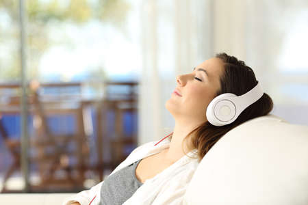 Foto de Side view portrait of a woman relaxing listening to music on a couch in the living room at home - Imagen libre de derechos