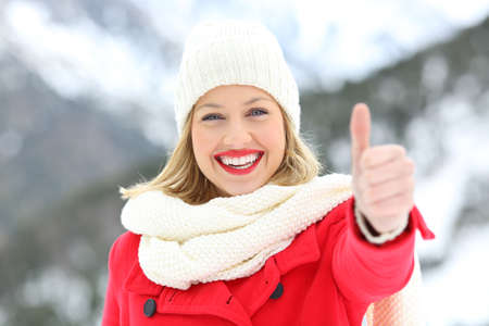 Photo for Front view portrait of a woman in red with thumbs up in winter with a snowy mountain in the background - Royalty Free Image