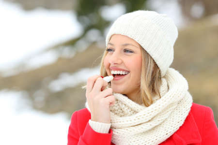 Photo for Girl protecting lips with lip balm in winter with a snowy mountain in the background - Royalty Free Image