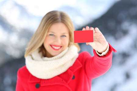 Foto de Front view portrait of a woman showing a credit card in winter with a snowy mountain in the background - Imagen libre de derechos