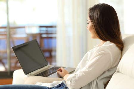 Foto de Serious woman using a laptop sitting on a sofa in the living room in an apartment interior - Imagen libre de derechos