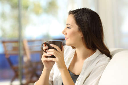 Photo pour Side view portrait of a serious pensive woman relaxing holding a coffee mug looking away sitting on a sofa in the living room in a house interior - image libre de droit