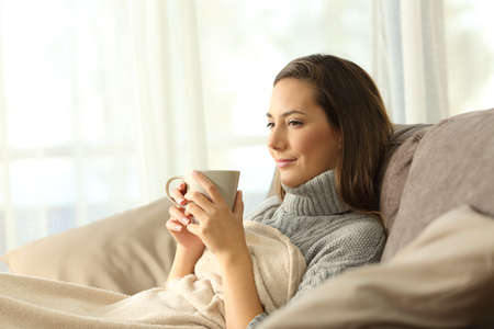 Photo for relaxed tenant resting holding a coffee mug sitting on a sofa in the living room in a house interior - Royalty Free Image