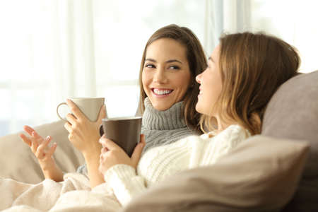 Photo pour Two happy roommates talking in winter sitting on a sofa in the living room in a house interior - image libre de droit