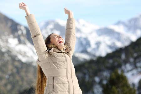 Foto de Excited woman raising arms celebrating success in the snowy mountain in winter - Imagen libre de derechos