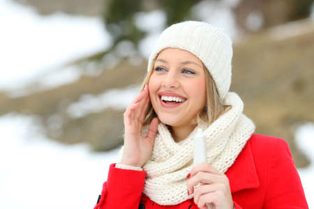 Photo pour Happy woman hydrating face skin with moisturizer cream in a snowy mountain in winter - image libre de droit