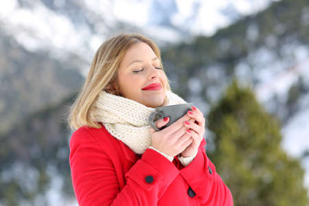 Photo for Portrait of a relaxed lady breathing fesh air and holding a coffee mug in a snowy mountain in winter - Royalty Free Image
