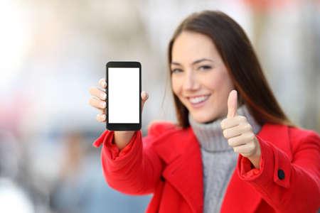 Foto de Woman showing a blank smart phone screen with thumbs up on the street in winter - Imagen libre de derechos