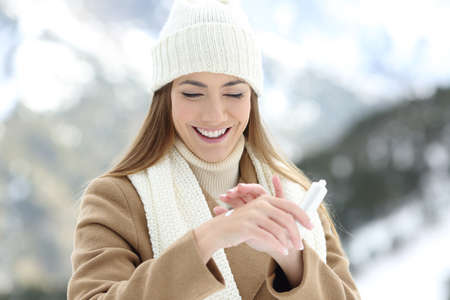 Foto de Front view portrait of a happy woman applying moisturizer cream to hydrate hands with a snowy mountain in the background - Imagen libre de derechos