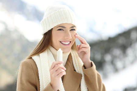 Foto de Portrait of a happy woman applying moisturize cream in face with a snowy mountain in the background - Imagen libre de derechos