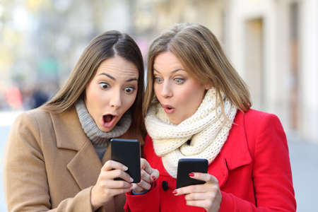 Foto de Front view portrait of two amazed women finding on line content on their smart phones on the street in winter - Imagen libre de derechos