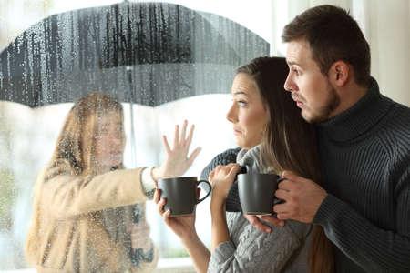 Foto de Stalker ex girlfriend disturbing to a couple that is relaxing looking through a window in a coffee shop - Imagen libre de derechos