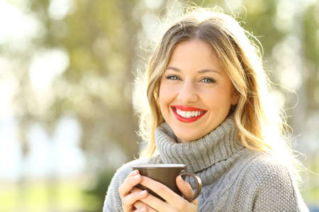 Photo for Happy woman wearing a grey jersey looking at camera holding a cup of coffee - Royalty Free Image