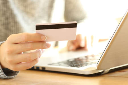 Photo for Close up of a girl hand using a credit card  to pay on line with a laptop on a desktop at home - Royalty Free Image