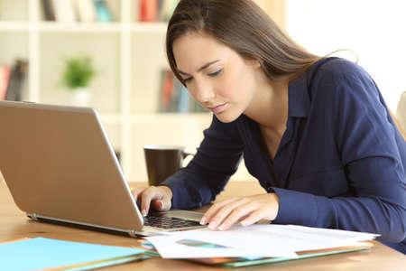 Foto de Concentrated entrepreneur comparing documents on line with a laptop sitting in a desktop at home - Imagen libre de derechos