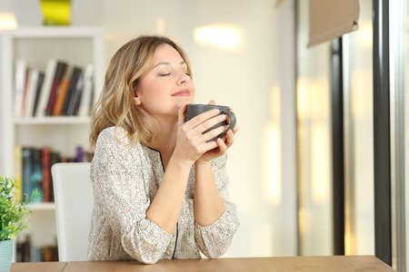 Foto de Portrait of a woman breathing and holding a coffee mug at home - Imagen libre de derechos