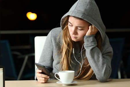 Foto de Portrait of a sad teen listening to music with a smart phone and earphones in a coffee shop in the night - Imagen libre de derechos