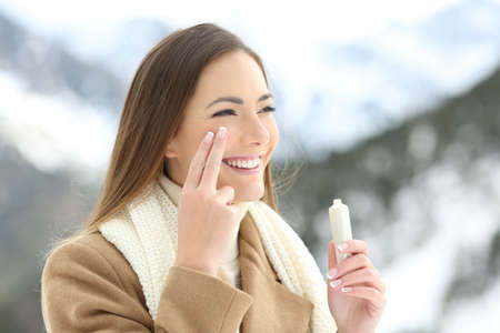 Foto de Portrait of a beauty happy lady applying facial moisturizer cream in winter - Imagen libre de derechos