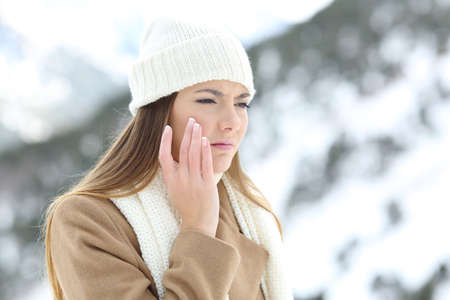 Photo pour Angry woman using a sking protection moisturizer cream in winter in a snowy mountain - image libre de droit