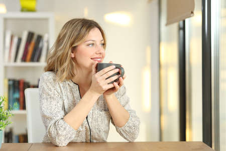 Photo pour Portrait of a woman looking through a window drinking coffee sitting in a table at home - image libre de droit
