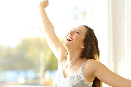 Foto de Portrait of an excited girl waking up in a sunny day raising arms beside a window - Imagen libre de derechos
