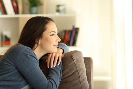 Photo pour Side view portrair of a satisfied pensive woman looking through a window sitting on a couch in the living room at home - image libre de droit