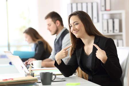 Foto de Portrait of a proud businesswoman pointing himself with both forefingers in a desk at office - Imagen libre de derechos