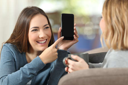 Photo pour Happy girl showing a blank phone screen to a friend on a couch at home - image libre de droit