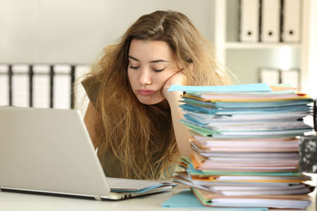 Photo for Exhausted intern with tousled hair working hard reading a lot of documents at office - Royalty Free Image