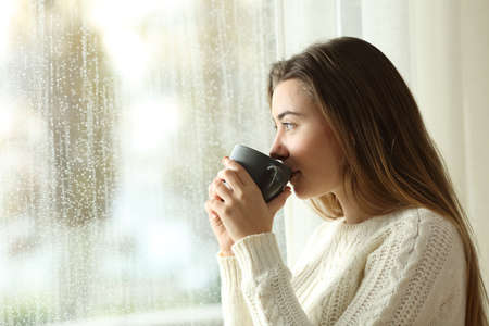 Foto de Side view portrait of a relaxed teen drinking coffee looking outside through a window in a rainy day of winter at home - Imagen libre de derechos