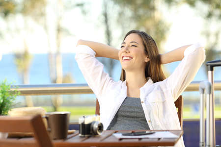 Photo pour Satisfied tourist enjoying vacations with arms in head outdoors in an hotel terrace - image libre de droit