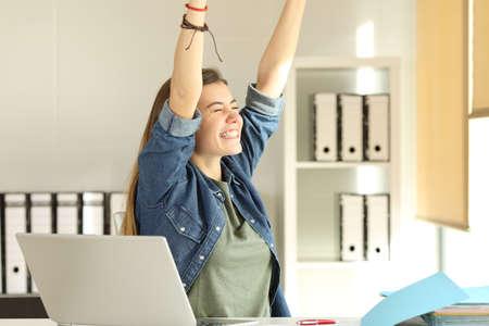 Foto de Portrait of a young satisfied intern raising arms at office - Imagen libre de derechos