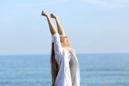 Foto de Side view portrait of an excited woman screaming and raising arms on the beach with the sea in the background - Imagen libre de derechos