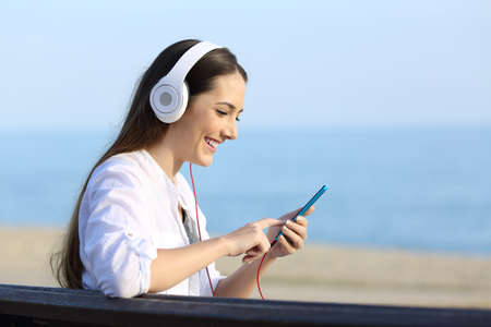 Photo pour Side view portrait of a happy woman listening to music wearing headphones sitting on a bench on the beach - image libre de droit