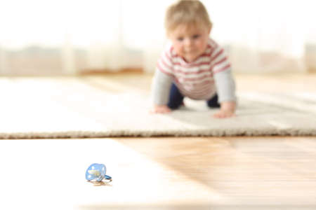 Photo pour Curious baby crawling towards a dirty pacifier on the floor at home - image libre de droit