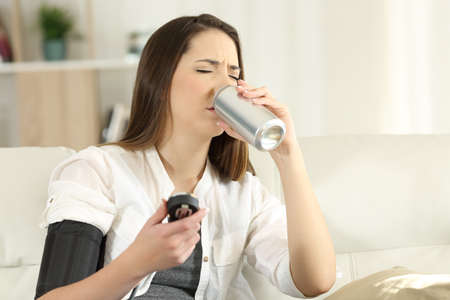 Photo for Woman suffering a low blood pressure drinking sweet soda sitting on a couch in the living room at home - Royalty Free Image