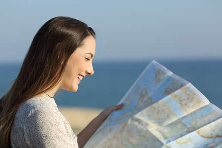 Foto de Side view portrait of a happy tourist reading a map on the beach - Imagen libre de derechos