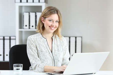 Photo for Portrait of a happy office employee working with a laptop and looking at camera - Royalty Free Image