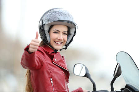 Photo for Satisfied motorbiker gesturing thumbs up on her motorcycle outdoors - Royalty Free Image