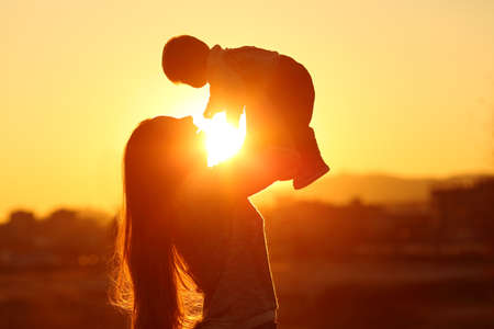 Photo for Backlight silhouette of a mother raising her kid son at sunset with the sun in the middle - Royalty Free Image
