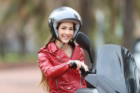 Photo for Happy biker wearing an helmet sitting on her motorbike looking at camera on the street - Royalty Free Image