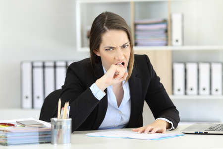Photo for Angry executive sitting in a desktop looking at camera at office - Royalty Free Image