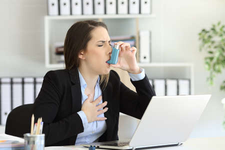 Photo for Asmathic executive having an asthma attack inhaling with a inhaler at office - Royalty Free Image