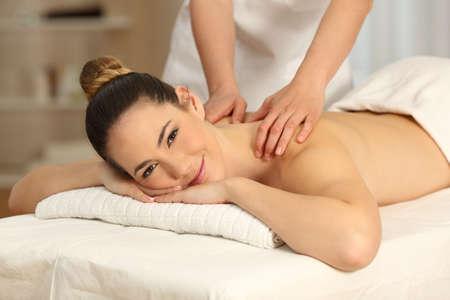 Photo pour Satisfied woman receiving a massage looking at camera in a spa salon - image libre de droit