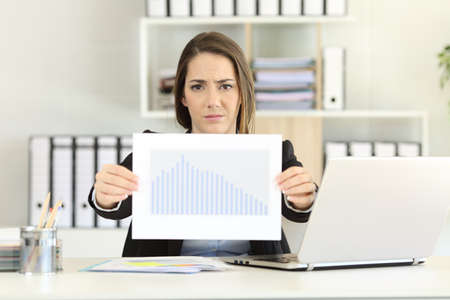 Photo for Front view of a worried executive showing a bad sales results chart at office - Royalty Free Image