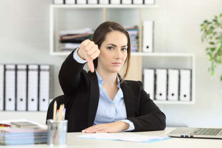 Foto de Front view portrait of an angry businesswoman denying with thumbs down at office - Imagen libre de derechos