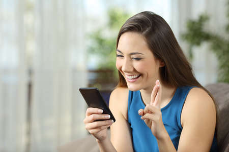 Foto de Hopeful woman waiting for online news in a smartphone sitting on a couch in the living room at home  - Imagen libre de derechos